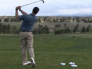 A person on the golf course implementing a swing change.